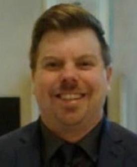 Justin Czujko - Headshot of man in suit smiling